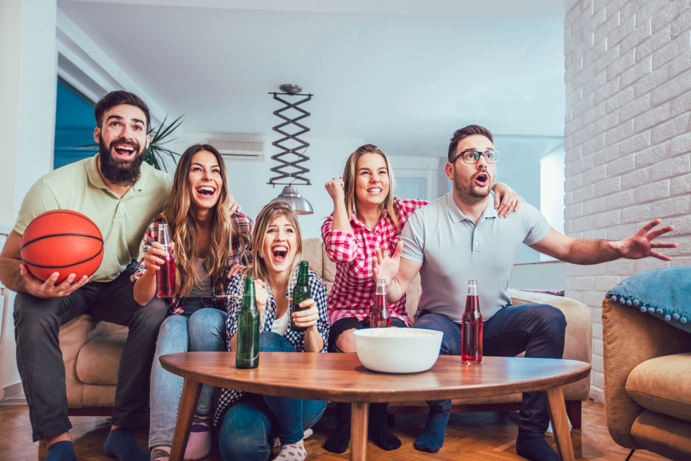 Shutterstock_1031764342 Happy friends or basketball fans watching basketball game on tv and celebrating victory at home.Friendship, sports and entertainment concept.