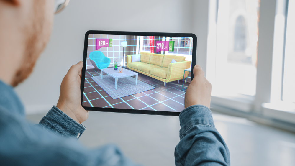 Shutterstock_1712828788 Decorating Apartment: Man Holding Digital Tablet with AR Interior Design Software Chooses 3D Furniture for Home from Online Shop with Shown Prices. Over Shoulder Screen Shot with 3D Render