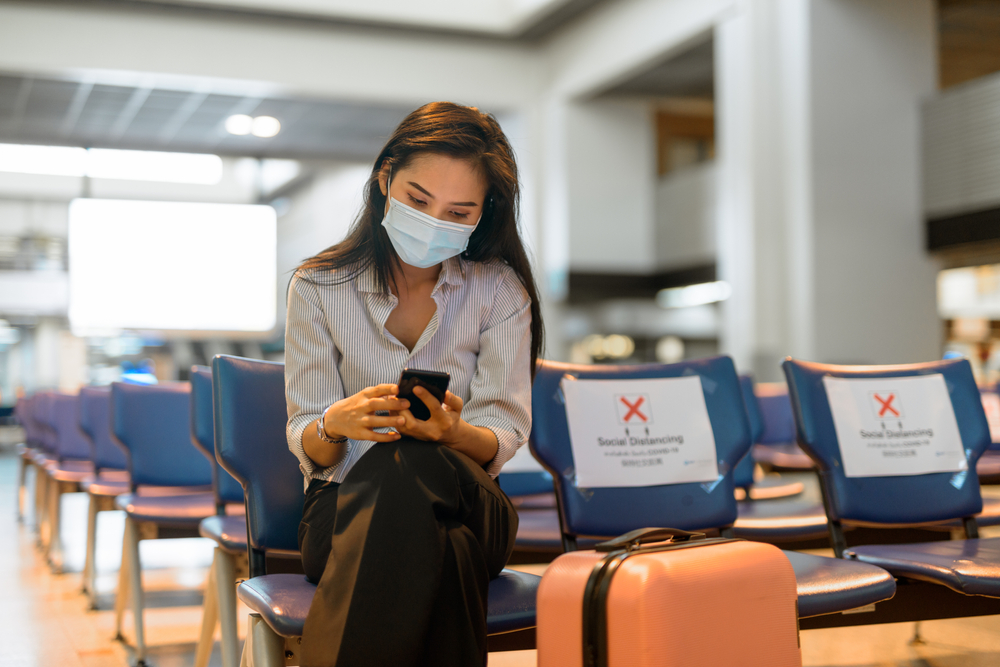Shutterstock-1710639979 Young Asian tourist woman with mask using phone and sitting with distance at the airport