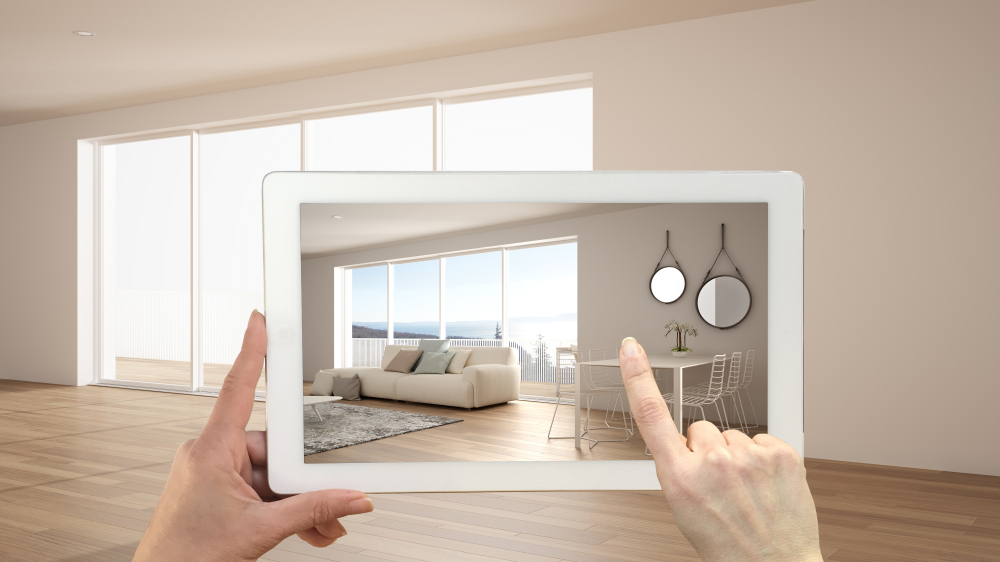 Shutterstock_1490086751 Augmented reality concept. Hand holding tablet with AR application used to simulate furniture and design products in empty interior with ceramic floor, modern white kitchen, 3d illustration