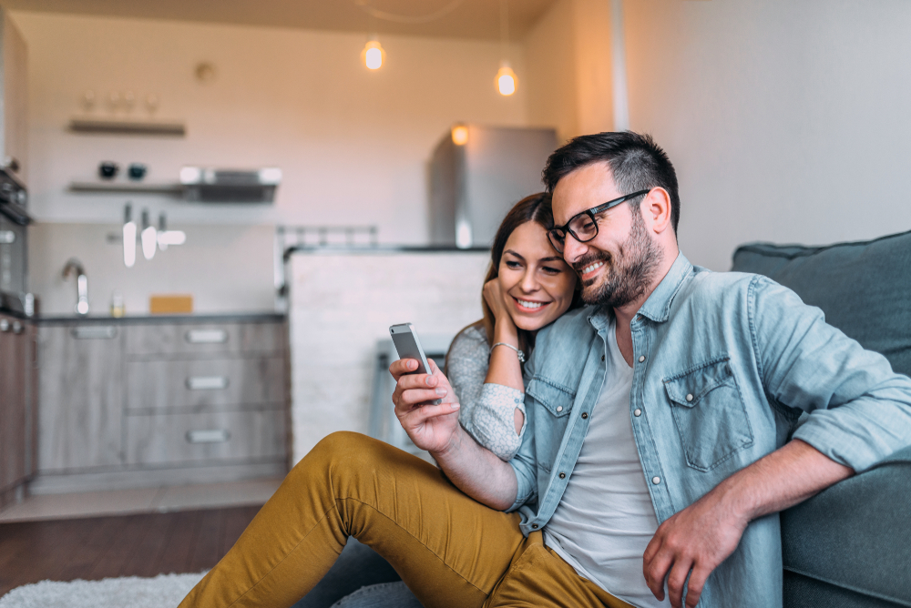 Shutterstock_1151804078 Close-up image of couple watching at smartphone screen indoors.
