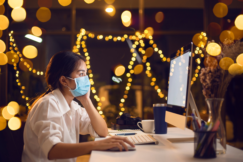Shutterstock_1700289517 Asian woman wear face mask for protection coronavirus (COVID 19). Asian woman quarantine working from home with computer on table in night light. Young Asian girl working at home in holiday festival.