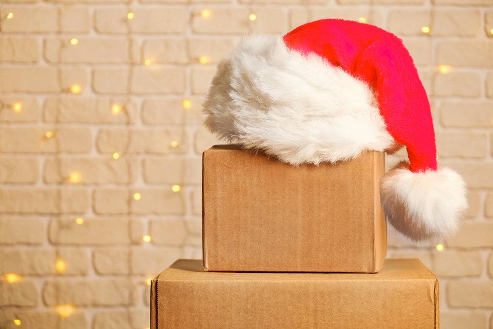 Shutterstock_1242289216 Blank brown freight box with Santa Claus hat on top, brick wall with Christmas lights on background. Moving company / delivery service holiday deals promotion concept. Copy space, close up.