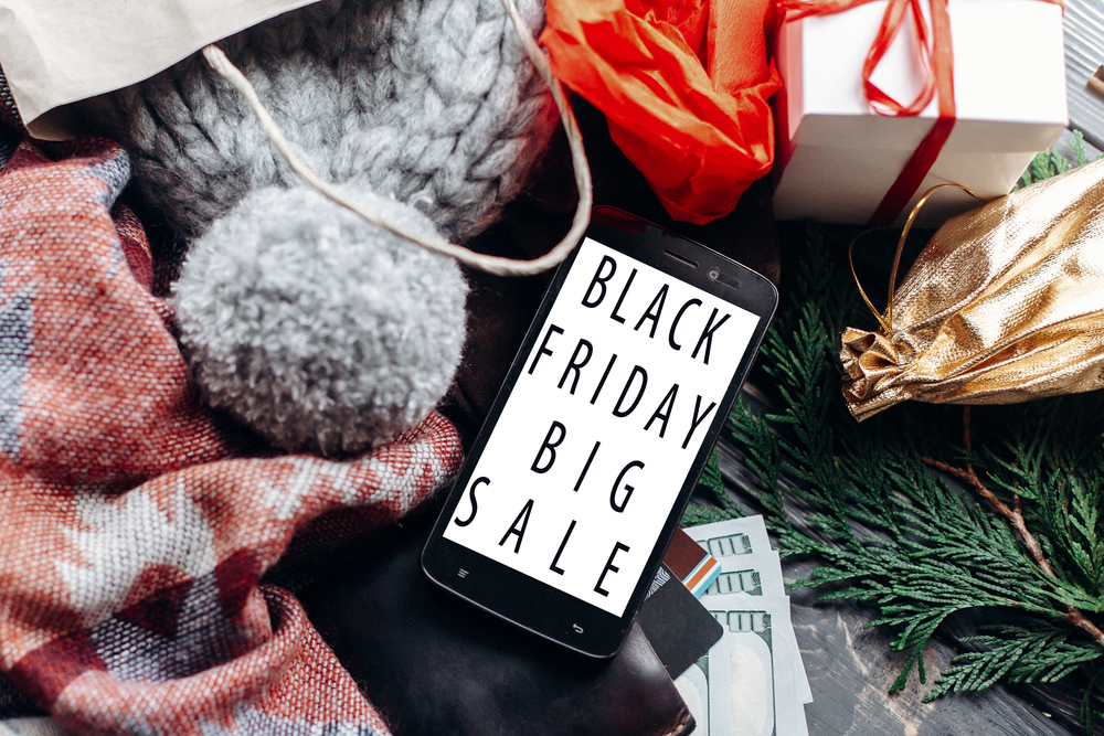 Shutterstock_521390977 black friday big sale. special christmas offer discount text on mobile phone screen message on seasonal rustic background with money cards wallet and bag with stuff and presents. advertising concept