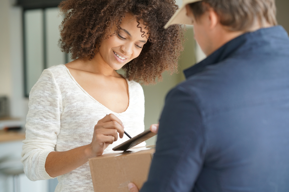 Shutterstock_513792328 Mixed race woman receiving package from delivery man