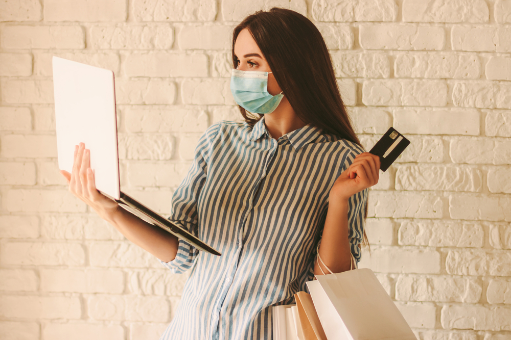 Shutterstock_1701052582 Young beautiful woman shopper in protective face mask hold laptop, credit card and shopping bags in hand. Happy girl in medical face mask shopping at online store. Coronavirus COVID-19, sale, discount