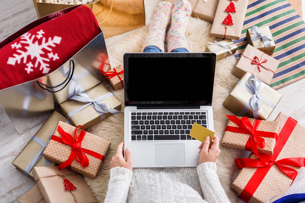Shutterstock_520967680 Christmas online shopping top view. Female buyer makes order on laptop with credit card, copy space on screen. Woman buy presents, prepare to xmas, among gift boxes and packages. Winter holidays sales