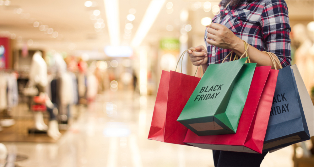 Shutterstock_1175980729 Black Friday, Woman holding many shopping bags while walking in the shopping mall background.