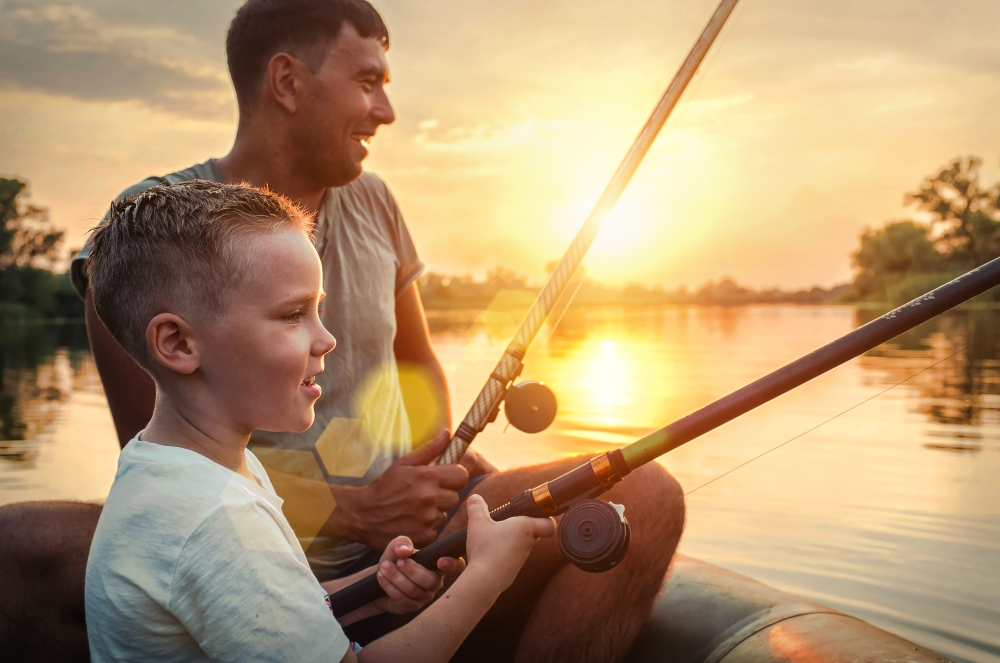 Shutterstock_1197062707 Happy Father and Son together fishing from a boat at sunset time in summer day under beautiful sky on the lake.