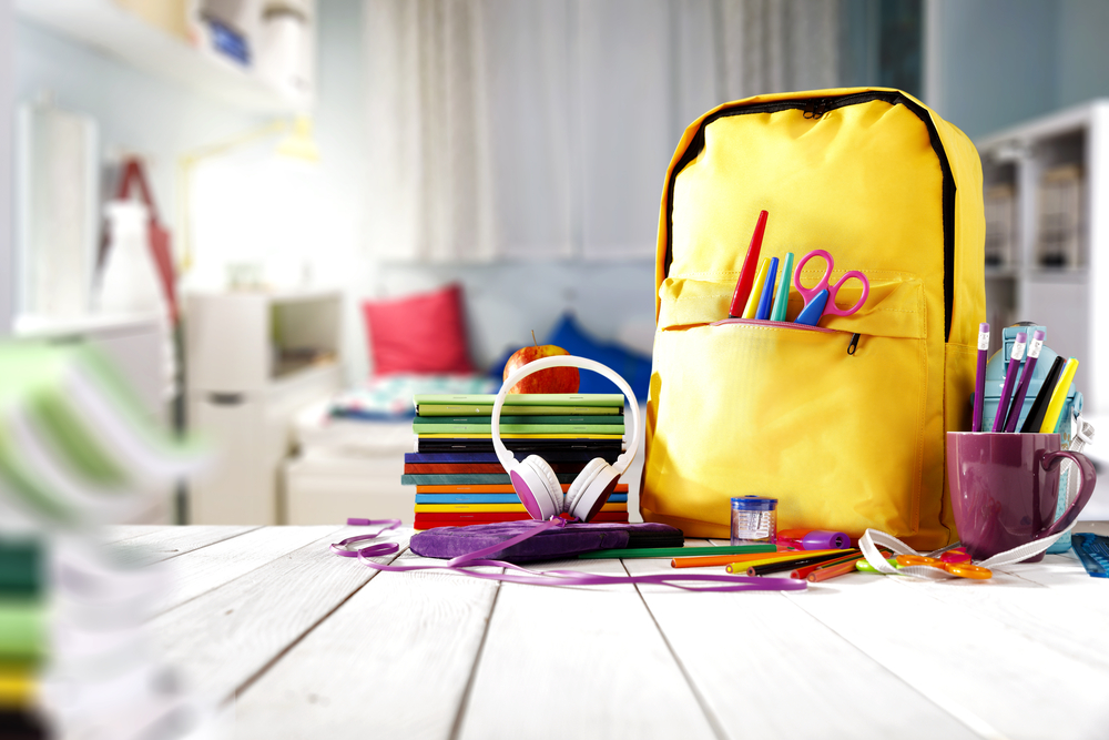 Shutterstock_702312109 School supplies on a wooden table in a warm interior