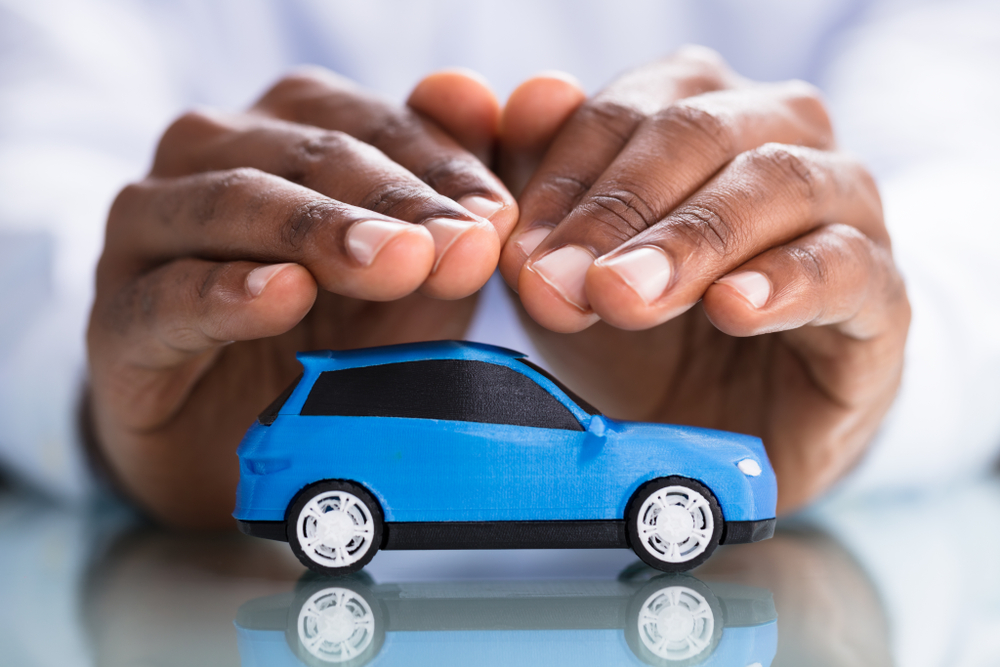 Shutterstock_1158955357 Businessman's Hand Protecting Blue Toy Car On The Reflective Desk