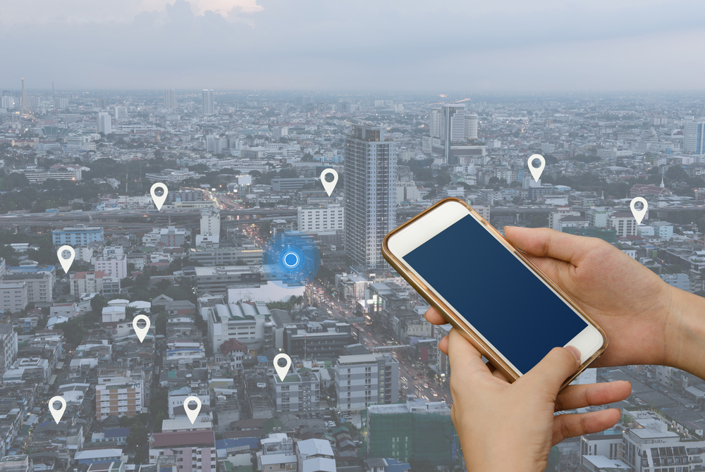 Shutterstock_529436278  Woman hand using mobile smartphone searching location on map and pin above blue tone city scape and network connection, internet of things, satellite navigation system app, smart journey concept
