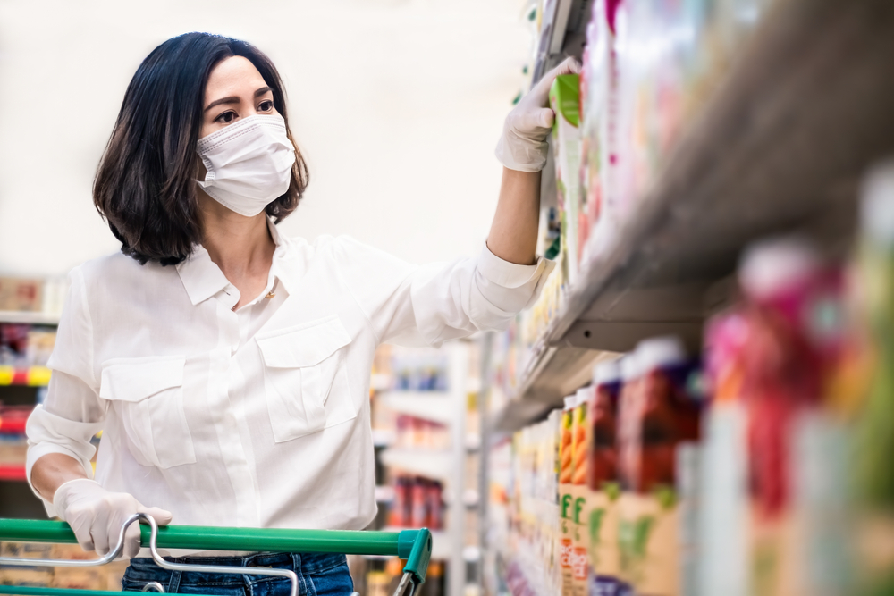 Shutterstock_1708963345 Asian woman wearing face mask and rubber glove push shopping cart in suppermarket departmentstore. Girl choosing, looking grocery things to buy at shelf during coronavirus crisis or covid19 outbreak.