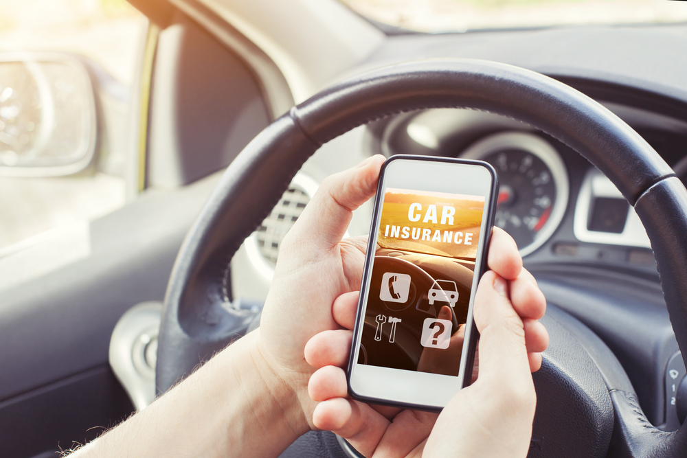 Shutterstock_703768939 car insurance concept, driver reading website on smartphone
