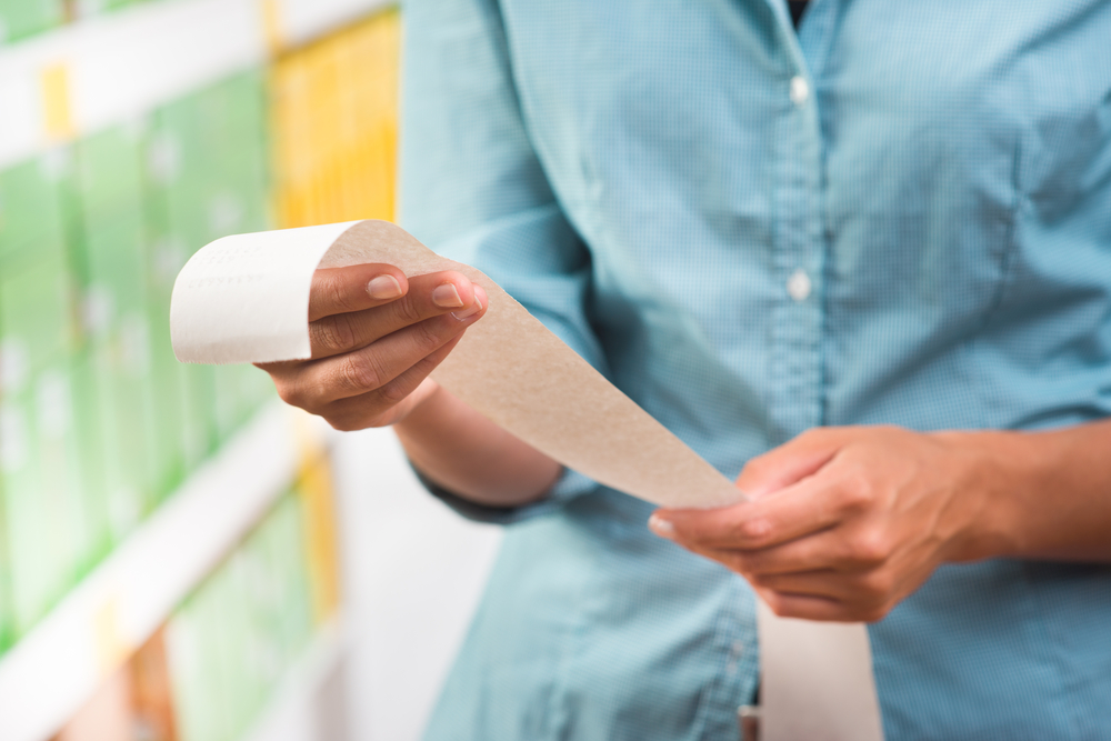 Shutterstock_210191599 Unrecognizable woman in light blue shirt checking a long grocery receipt at store.