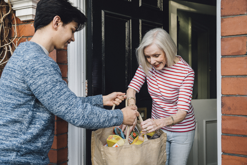 Shutterstock_638686714 Teenage boy is delivering some groceries to an elderly woman. He is handing her a shopping bag at her front door.
