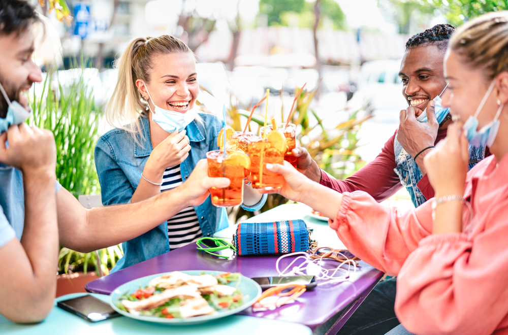 Shutterstock_1744841810 Friends drinking spritz at cocktail bar with face masks - New normal friendship concept with happy people having fun together toasting drinks at restaurant - Bright end filter with focus on left woman