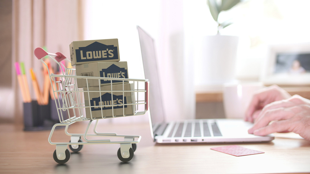 Shutterstock_1742195450 Cartons with LOWE'S logo in shopping trolley near customer with laptop. Editorial online shopping from home 3D rendering