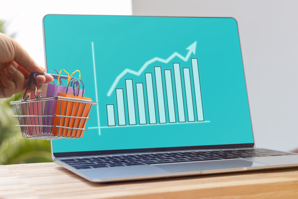 Shutterstock_1456690535 Hand holding shopping basket on laptop keyboard with graph growth and increase of chart on screen. Consumer can buy product directly anywhere anytime from seller. Online shopping and ecommerce concept