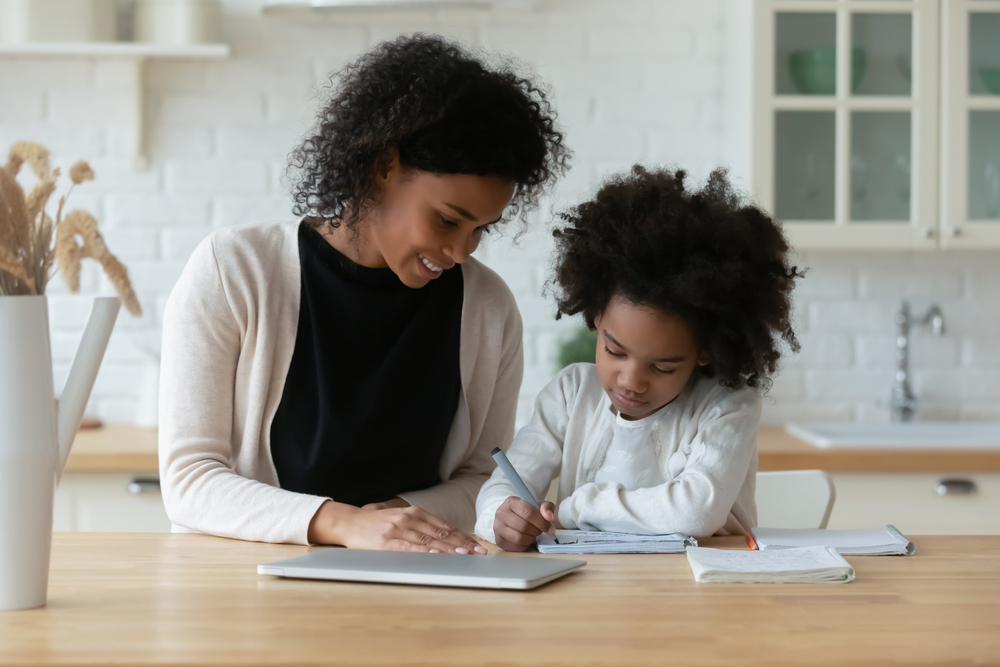 Shutterstock_1707844084 African American young mother and little daughter sit at desk in kitchen studying online together, biracial mom and small girl child handwrite, do homework, learning at home, homeschooling concept
