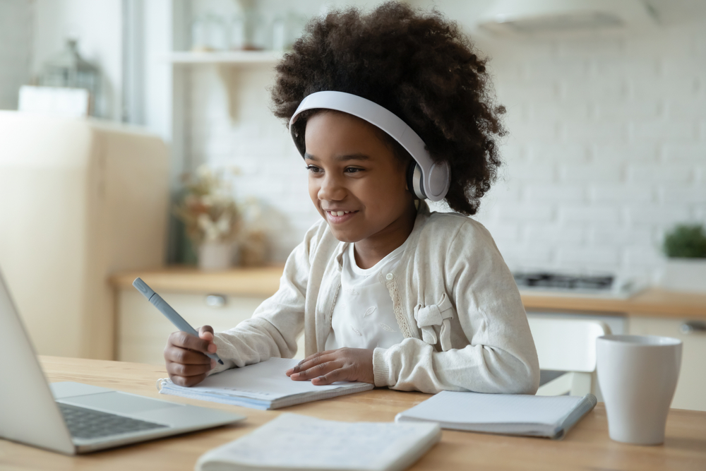 Shutterstock_1707844081 Smiling small African American girl in headphones watch video lesson on computer in kitchen, happy little biracial child in earphones have online web class using laptop at home, homeschooling concept