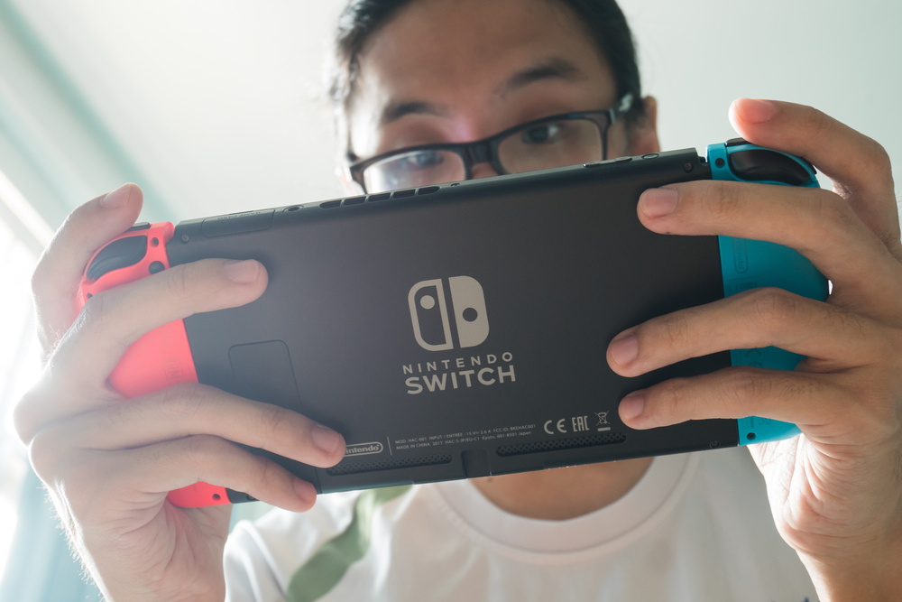 Shutterstock_745971748 Bangkok, Thailand - October 31, 2017 : A man playing Nintendo Switch.