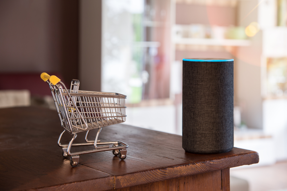 Shutterstock_1558514012 Shopping cart and smart speaker with voice recognition. In the living room simply by voice command goods shopping.