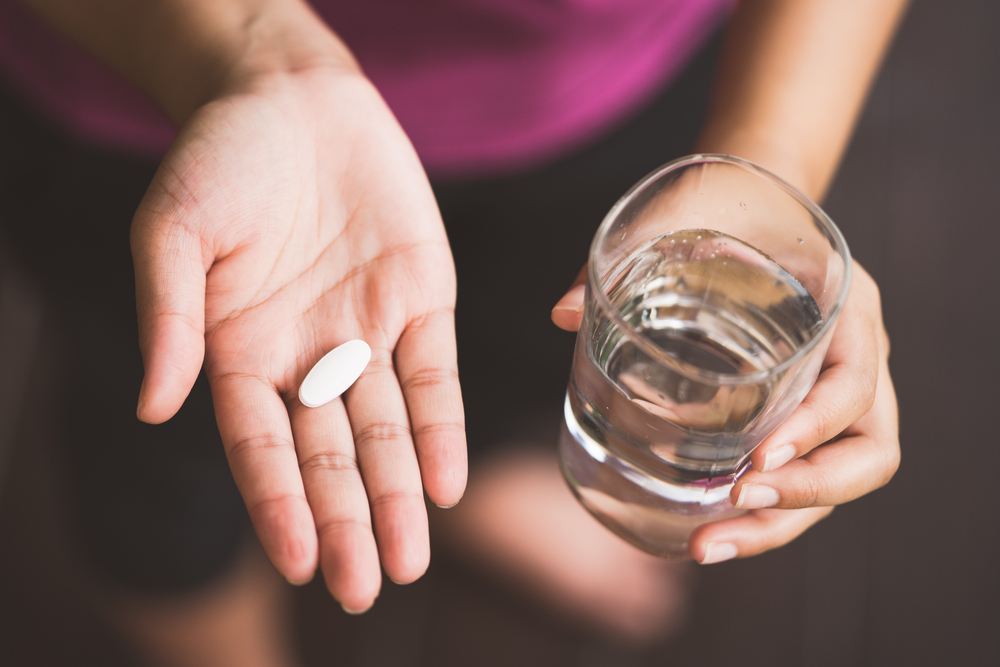Shutterstock_718784776 Close Up Of Girl holding Pill and glass of water.With Paracetamol.Nutritional Supplements.Sport,Diet Concept.Capsules Vitamin And Dietary Supplements.