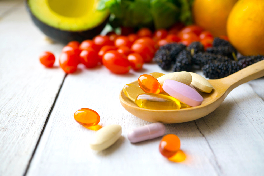 Shutterstock_1041373417 Pills and capsules in wooden spoon with fresh fruits. Multivitamins and supplement from fruits concept.