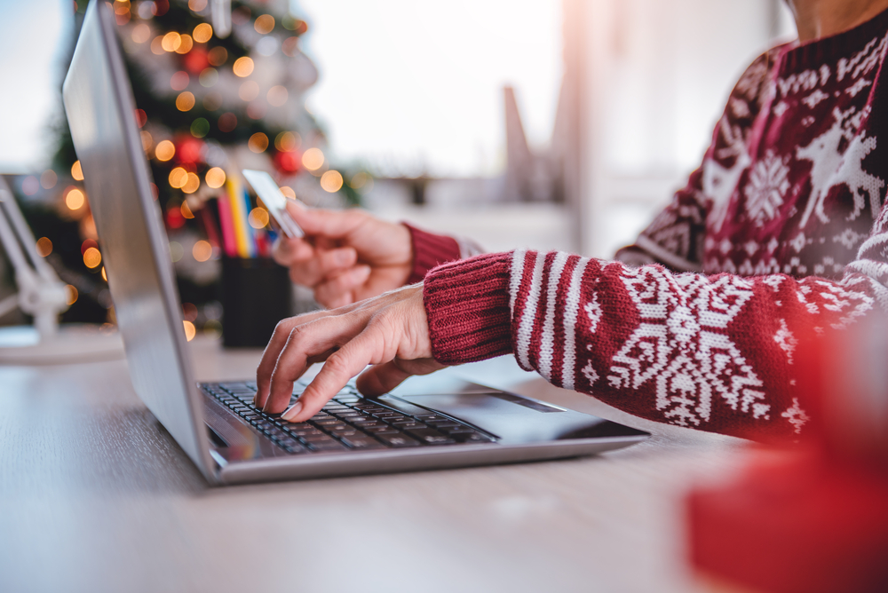 Shutterstock_753208630 Women wearing red sweater shopping online and using credit card at home office