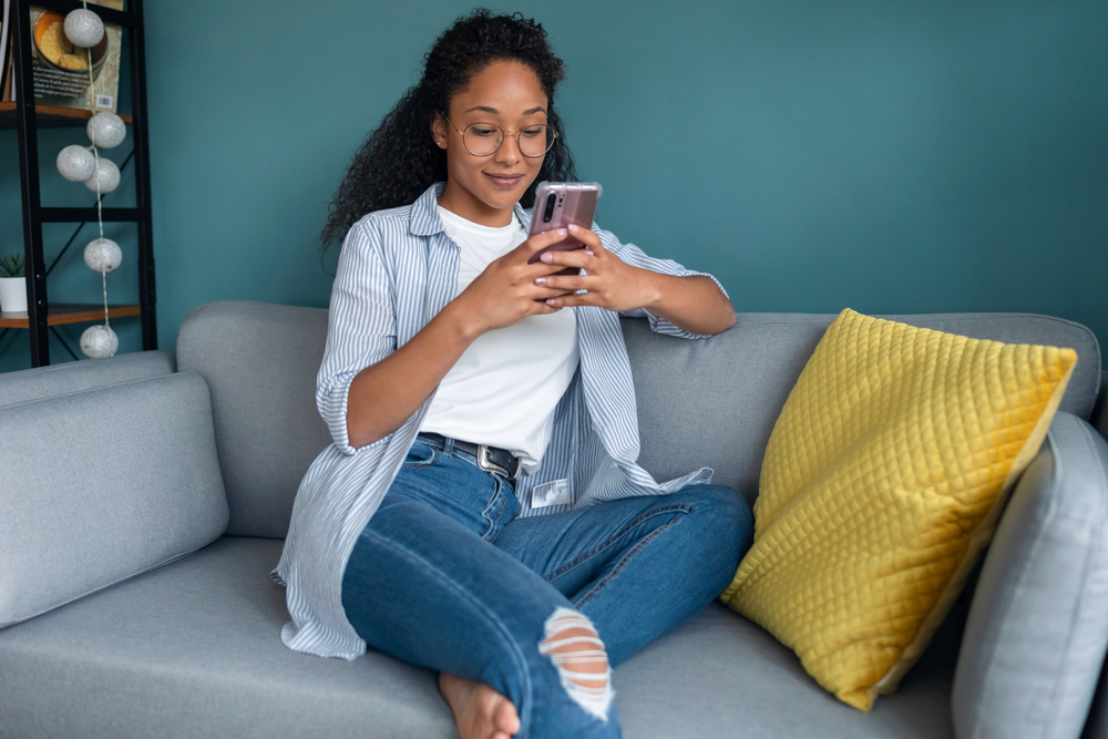 Shutterstock_1787788901 Shot of smiling young african american woman using her mobile phone while sitting on sofa at home.
