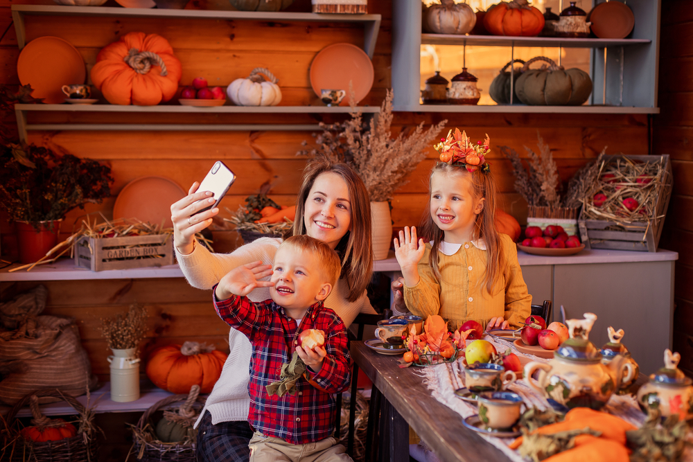 Shutterstock_1829187983 Family congratulates friends on Thanksgiving online. Video chatting with friends new normal. Festive dinner remotely by phone on a smartphone. Social distance pandemic covid-19. Celebrating tradition
