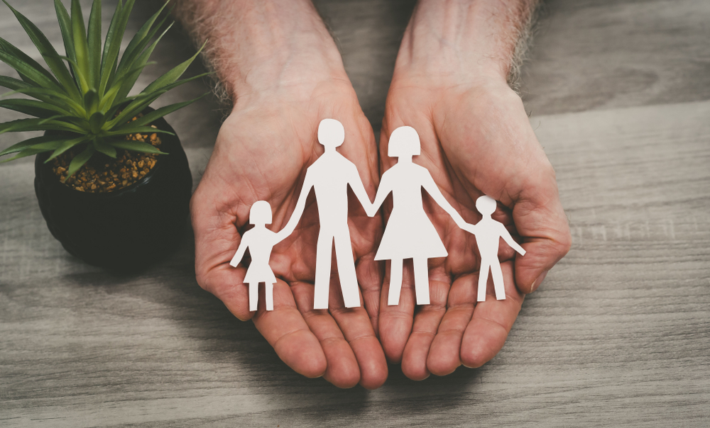 Shutterstock_1573350688 Hands protecting a family; symbol of life insurance