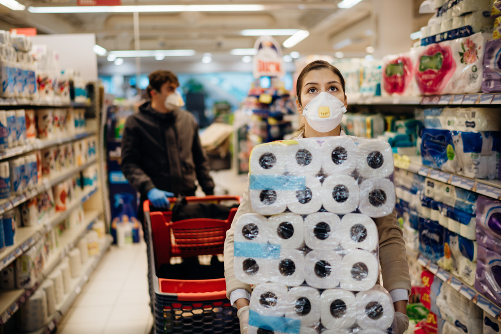 Shutterstock_1688252590 Woman shopper with mask and gloves panic buying and hoarding toilette paper in supply store.Preparing for pathogen virus pandemic quarantine.Prepper buying bulk cleaning supplies due to Covid-19.