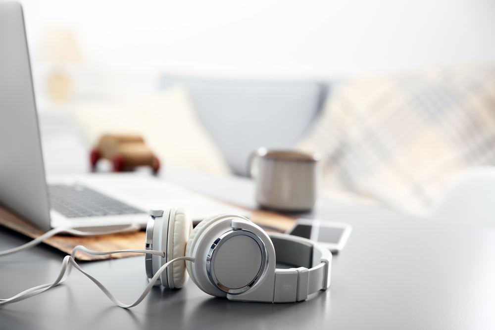 Shutterstock_366639842 Headphones, phone and laptop on white table against defocused background