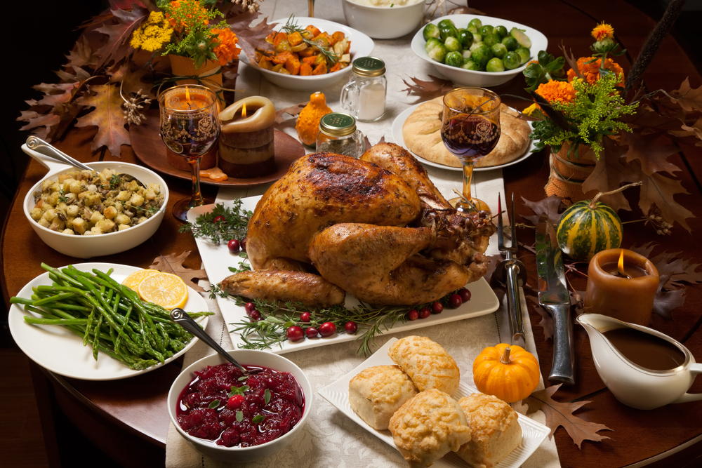 Shutterstock_335079266 Roasted turkey garnished with cranberries on a rustic style table decoraded with pumpkins, gourds, asparagus, brussel sprouts, baked vegetables, pie, flowers, and candles.