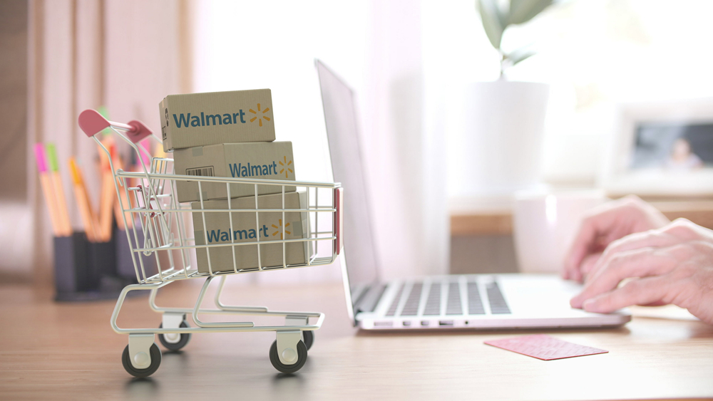Shutterstock_1696873096 WALMART logo on boxes in shopping cart near the laptop. Editorial online shopping from home 3D rendering