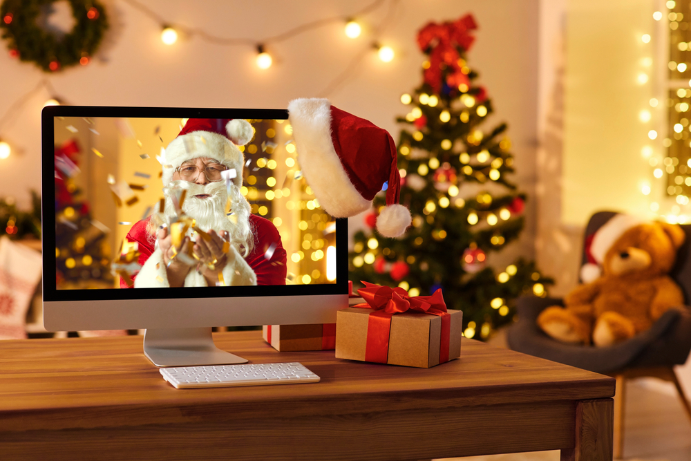Shutterstock_1841199370 Computer on table in cozy room with hanging red hat and with Santa Claus on screen blowing golden confetti, sending love, wishing Merry Christmas and Happy New Year online and making miracle come true