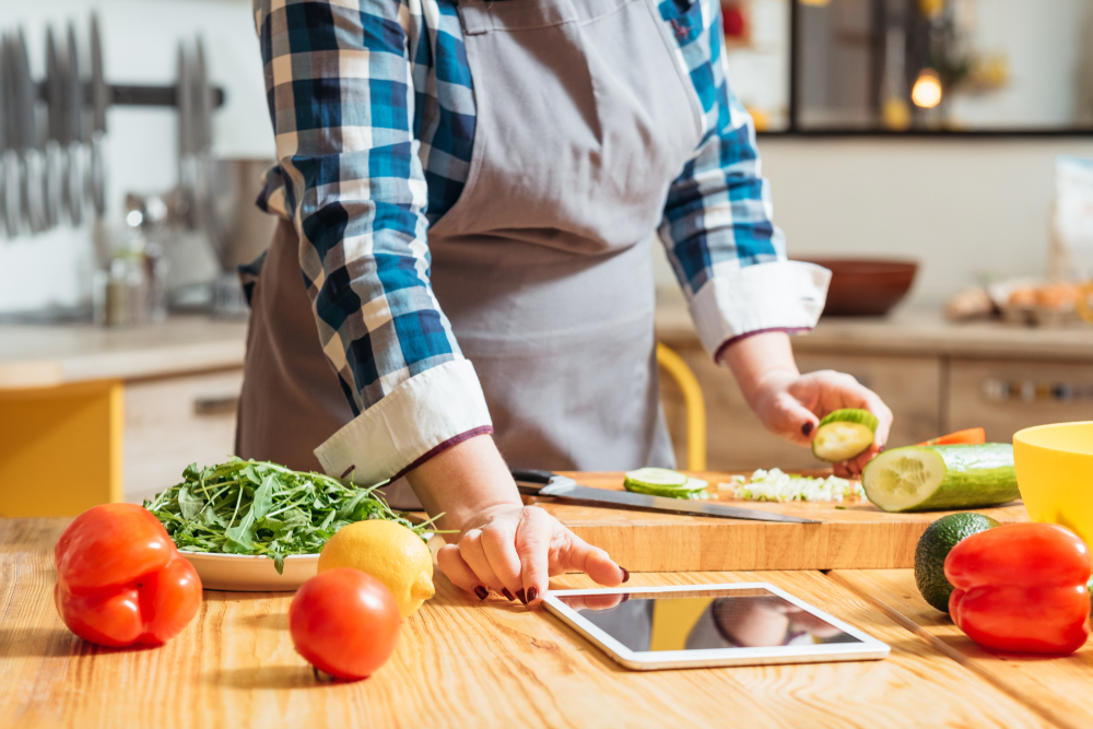 Shutterstock_1402487315 Healthy diet. Woman watching online culinary class on her tablet, making salad with fresh vegetables. Vegetarian food.