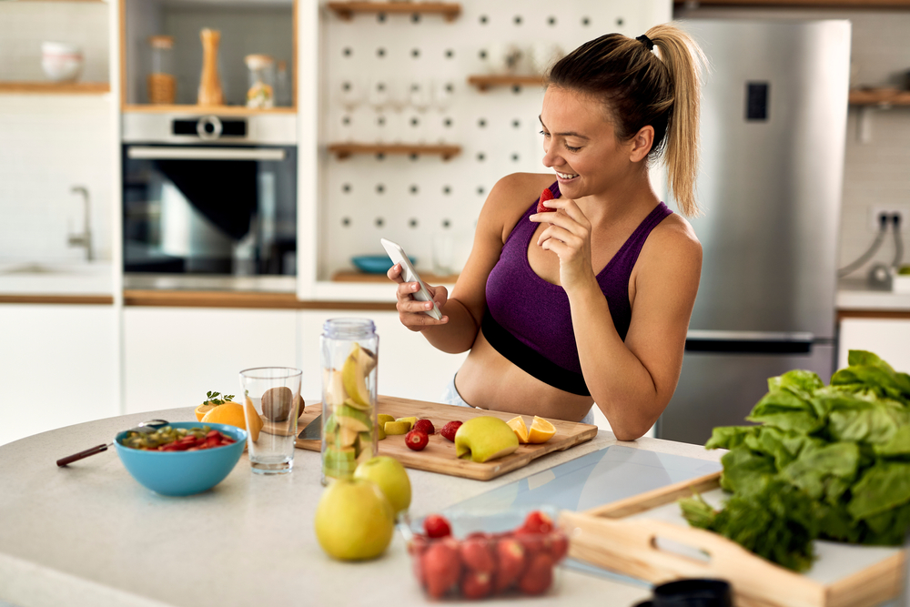 Shutterstock_1745003447 Young happy athletic woman eating fruit while text messaging on mobile phone in the kitchen.