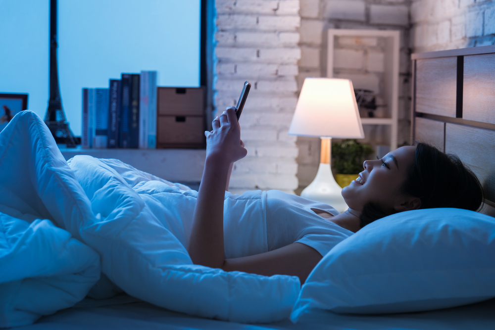 Shutterstock_736958713 Asian women are using the smart phone on the bed before she sleeping at night. Mobile addict concept.