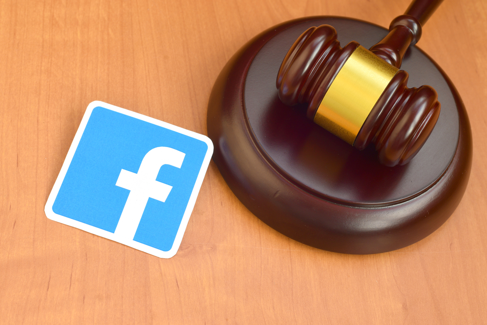 Shutterstock_1698112588 Facebook paper logo lies with wooden judge gavel. Entertainment lawsuit concept