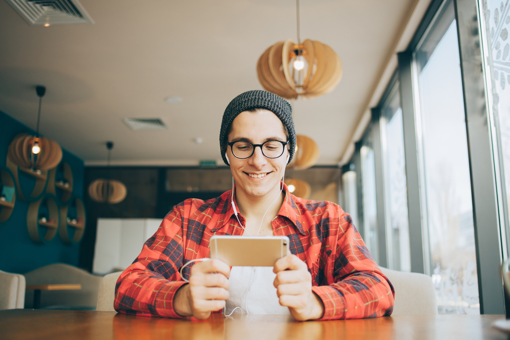 Shutterstock_562571530 Attractive young man is sitting in office and drinking tea. He is holding a mobile phone and watching video or reading interesting article. Handsome guy is smiling