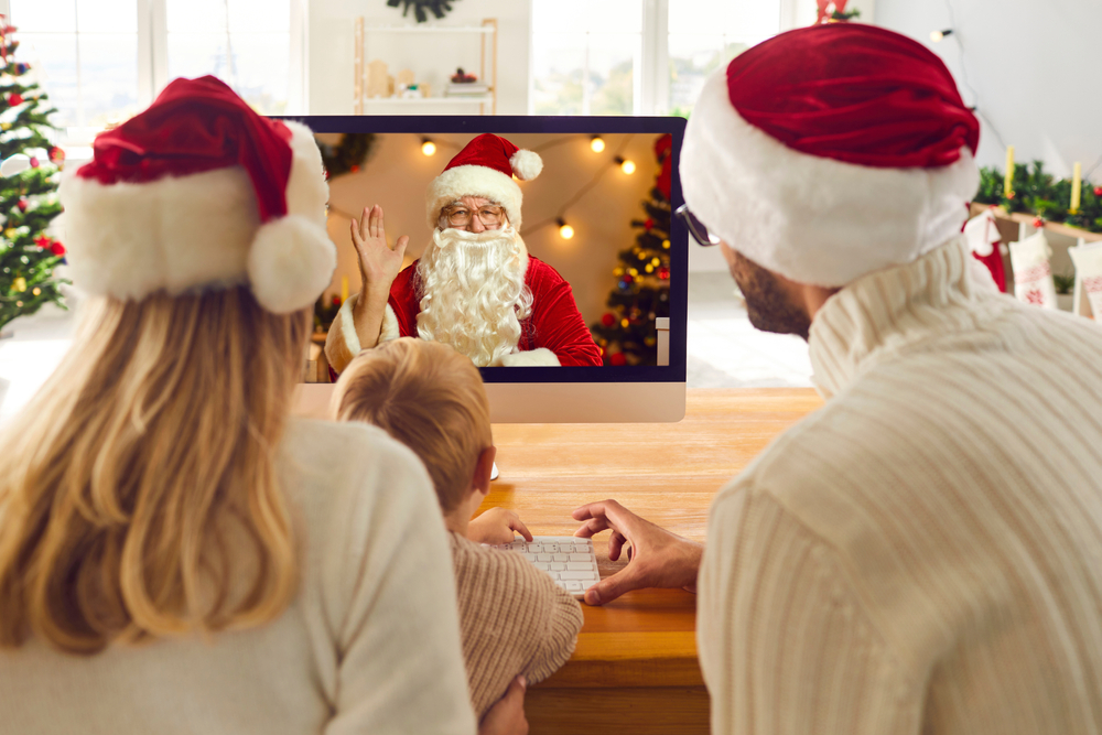 Shutterstock_1833940126 Young family staying at home on Christmas holidays and having online lockdown party. Mom, dad and son looking at computer screen during video call with Santa Claus who's waving hand to greet them