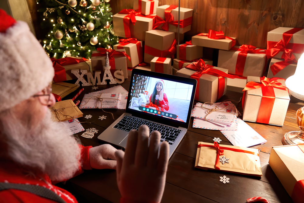 Shutterstock_1837824535 Over shoulder view of Santa Claus video calling kid girl on laptop greeting child by webcam talk open Christmas gift box by virtual online videocall using computer sit at workshop table on xmas eve.