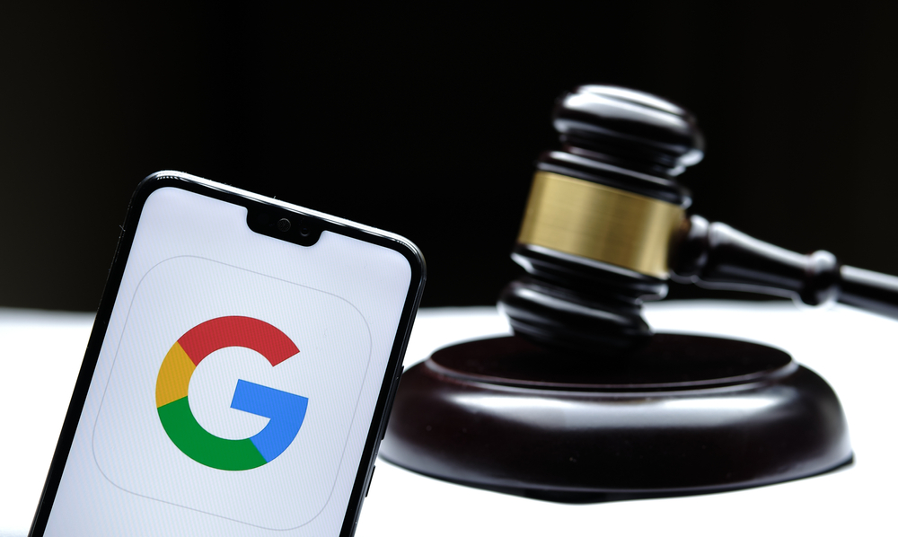 Shutterstock_1875389428 Stafford, United Kingdom - December 15 2020: Google logo seen on the smartphone placed next to the judges gavel. Concept for a lawsuit, legal case, antitrust and fine. Real photo, not a montage.