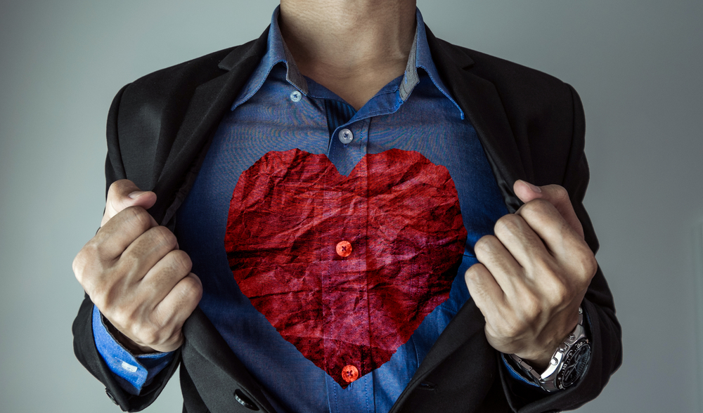 Shutterstock_440044309 a guy in suit opening his suit showing red crumpled heart shape