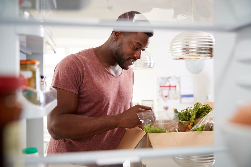 Shutterstock_1459832249 View Looking Out From Inside Of Refrigerator As Man Unpacks Online Home Food Delivery