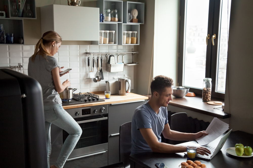 Shutterstock_1156208539 Young couple using laptop and smartphone in the kitchen, smiling man working online at home while his wife cooking with phone apps, family morning lifestyle with gadgets or devices addiction concept
