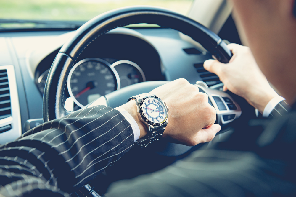 Shutterstock_368989106 Man driving a car and looking at watch ,business concept ,vintage tone